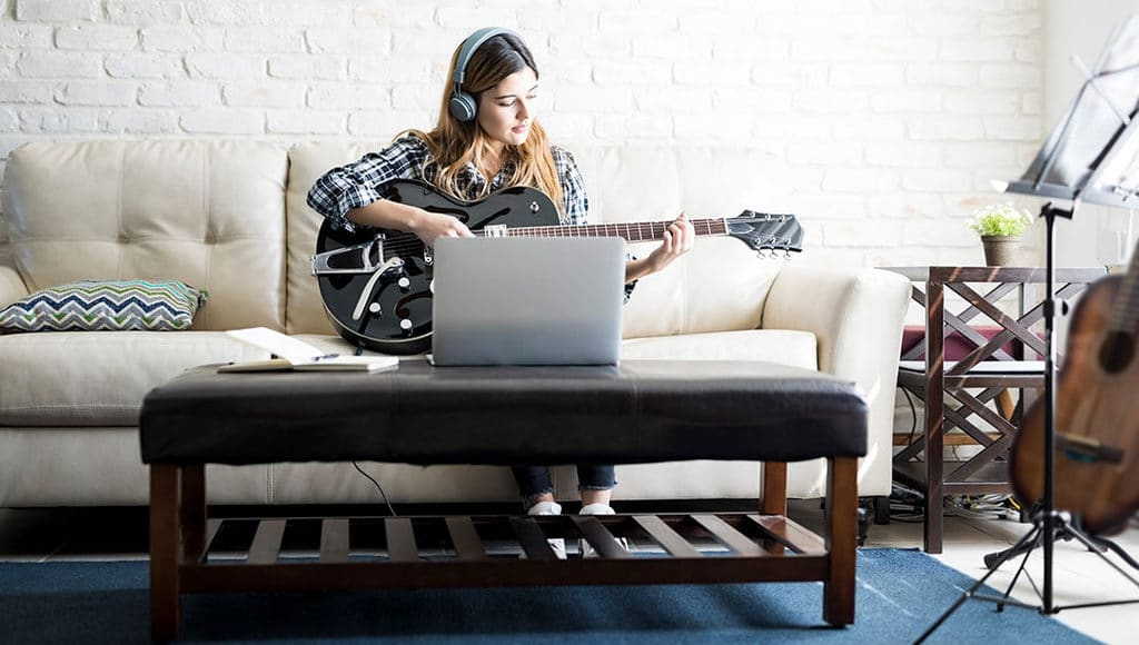 woman playing guitar with headphones