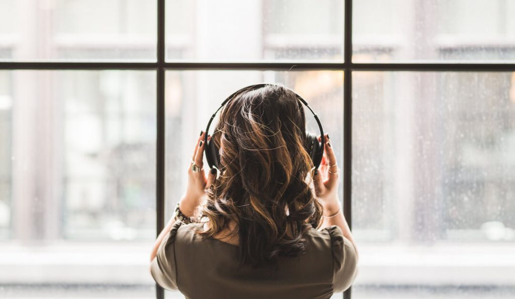 woman wearing headphones at window