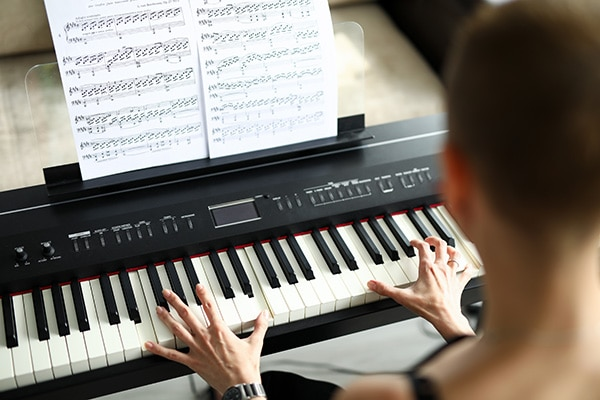woman playing digital piano
